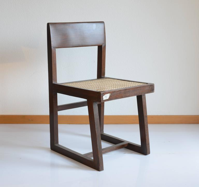 """Chair in solid teak and braided canework. Solid """"banner"""" type backrest, slanted and slightly curved. Asymmetric """"frame"""" type canework seat and double leg assembly, with the legs connected by two rails, circa 1960. Great restored. Cane has been"""