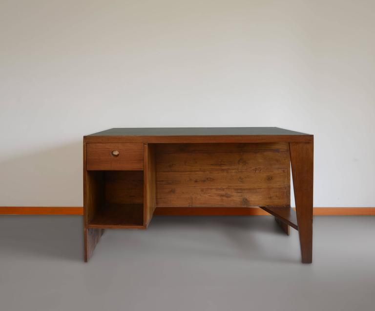 Office desk, 1957-1958. Rectangular top covered in black leather on a frame, affixed on one side by a panel forming a left side leg with a box section including a drawer and compartment and on the other side, a profiled leg with a flat triangular