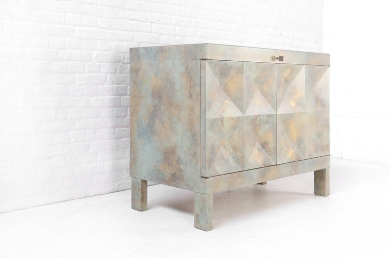 Small drinks cabinet in excellent quality. Its very unusual to see them with bronze patina. This small dry bar shows absolutely stunning graphical patterns on its doors. Squares, crosses, triangles and diamonds are combined to form a spectacular