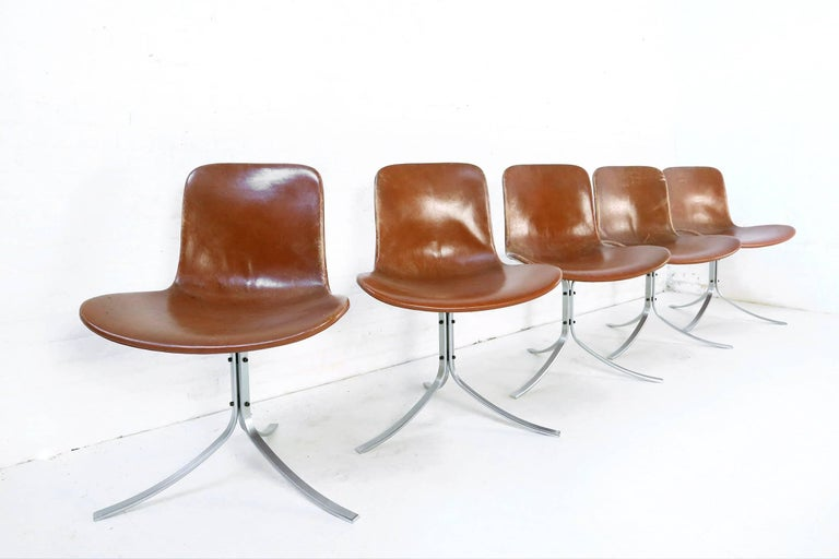 This iconic and first edition set of five PK-9 chairs was designed by Poul Kjaerholm and produced by E. Kold Christensen in the 1960s. The chairs feature their original patinated cognac leather upholstery. There is a maker's mark on the three curved