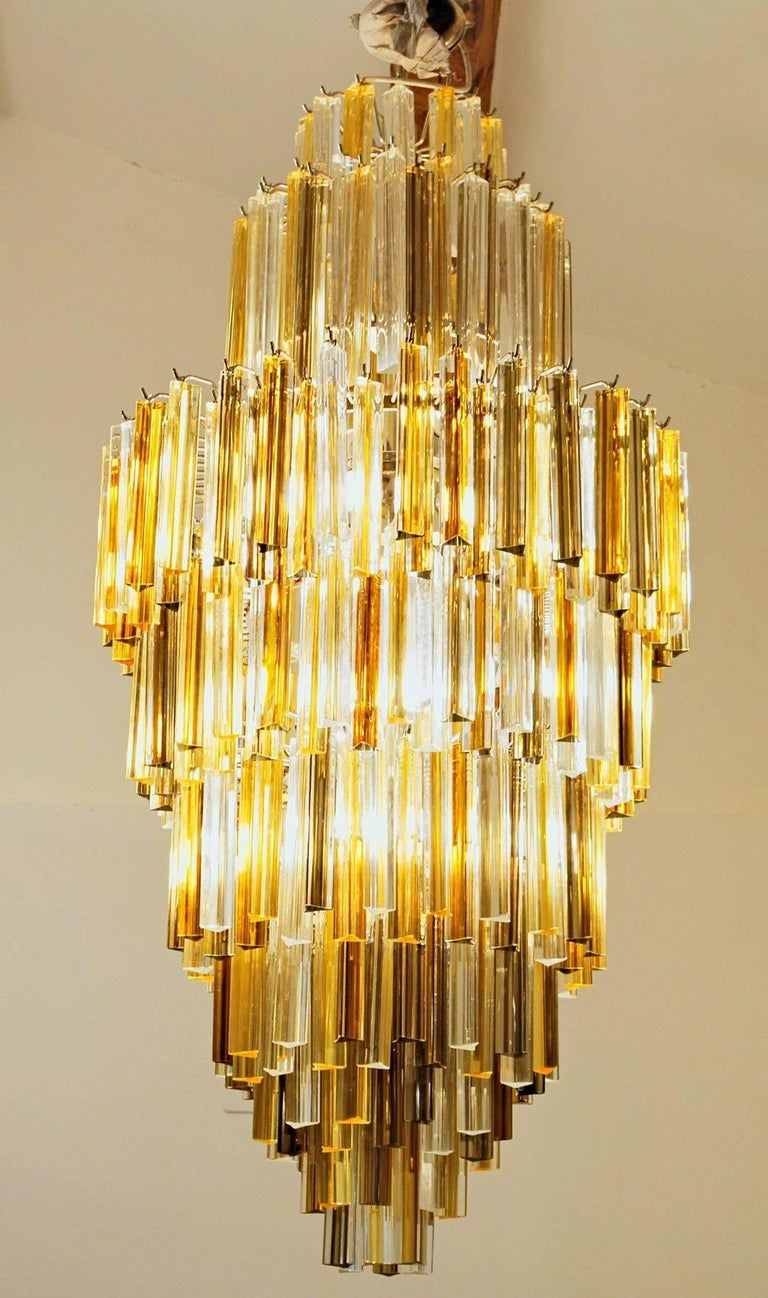 This chandelier has 342 elements of triedri elements. There is a combination of clear, amber and deep amber triedri. The mix gives a sculptural art dimension to this mid-century modern chandelier.  The polished ends are creating a remarkable effect.