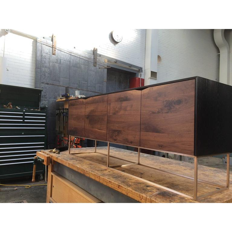 Handcrafted Classic modern credenza of select American hardwoods with a solid bronze base. Ebonized ash cabinet with four walnut soft-closing doors and a solid bronze base. Each compartment has an adjustable shelf. Great for media use or simply as a