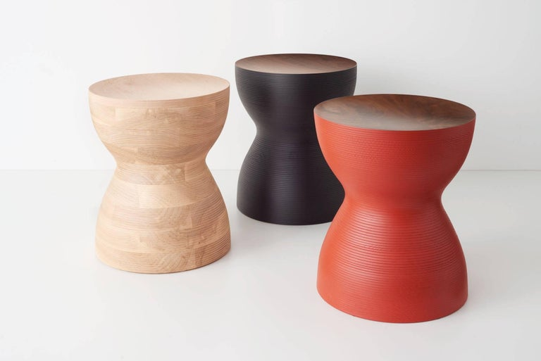 Stacked lamination of ash hardwood with a maple top, turned on a lathe. This pleasing sculptural object can be used as a side table or stool for seating. They look great in this natural finish or in colors - blue, red, or black. They are made of