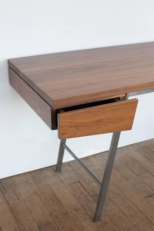 Spare, refined, and meticulously handcrafted of solid hardwoods and bronze, the AD7 desk is distinguished by superb detailing, the finest materials and timeless design. The composition plays with the relationship between positive and negative space,