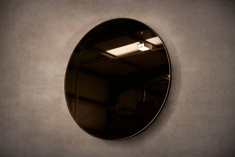 Wall-mounted circular mirror with blackened steel frame. Bronze or grey tinted glass available. Supplied with two screw fixing points to rear face. Handcrafted in the North East, England.  Measures: 80cm (diameter) x 2cm (depth). Custom sizes