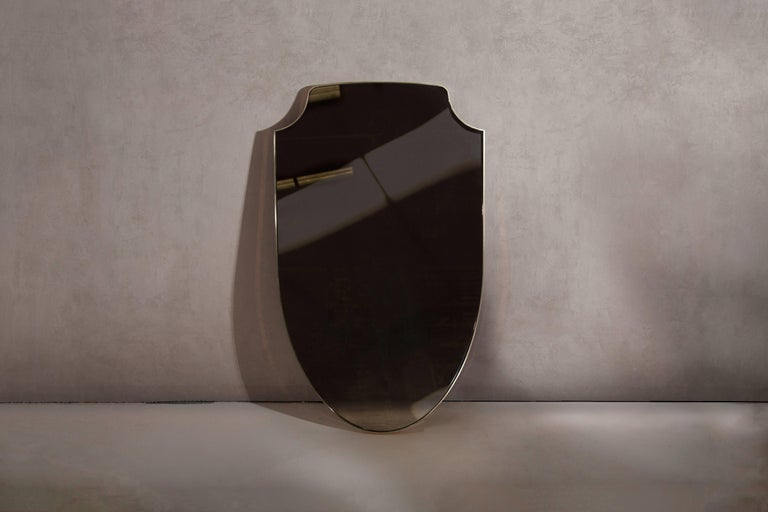 Minimal shield mirror in brass. Handcrafted in North East, England.  Measures: 91.5cm height x 53cm width x 2cm depth. Custom sizes available.  Made to order in 3-4 weeks. Price includes VAT.