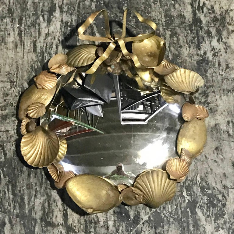 Pair of French brass shell motif convex mirrors, each one with a continuous surround of seashells, holding a 9.5 inch convex mirror, joined with a ribbon atop. This item is at our Atlanta GA, Location, not Palm Beach.