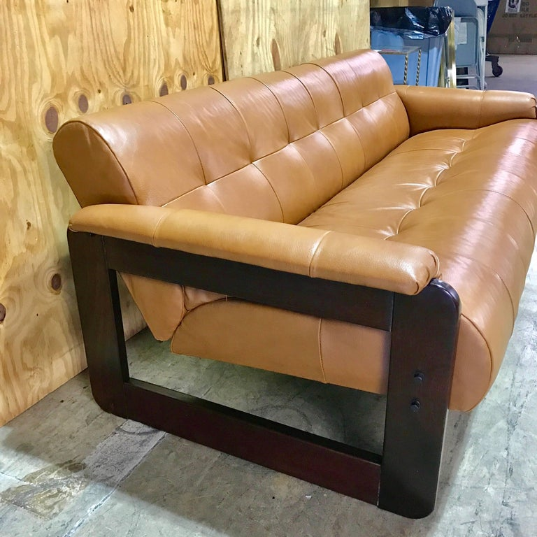 Brazilian rosewood and saddle leather long sofa by Percival Lafer. Clean lines with luxurious camel leather rolled arms, on rosewood cube frames. The backs are finished in brown suede. This sofa retains its original label, numbered 11875. The arm