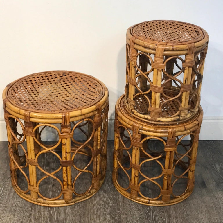 Set of three Graduating/ Nesting bamboo, rattan and reed nesting side tables, each one woven with interlocking circles and a caned top. Measure: 13