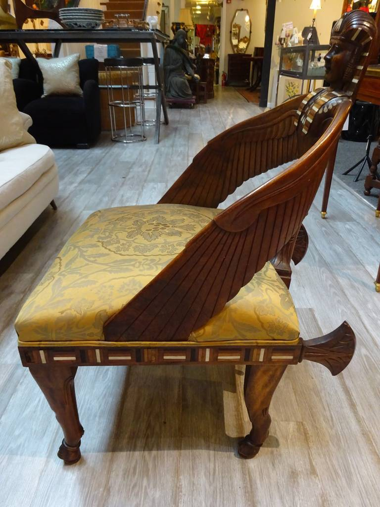 A beautiful Egyptian Revival English mahogany chair with carved sphinx and pearl, bone and ebony inlaid decoration.