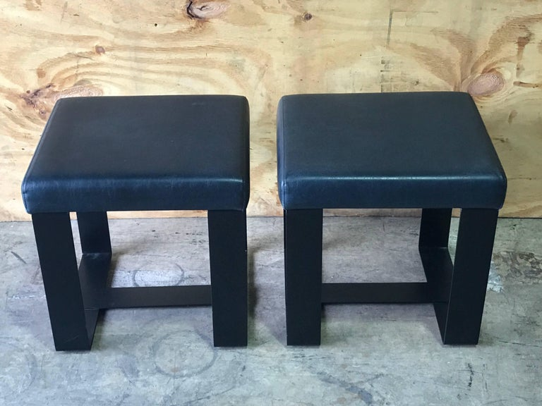 Pair of French modern iron and leather cube benches, each one with leather upholstered seat raised on a iron