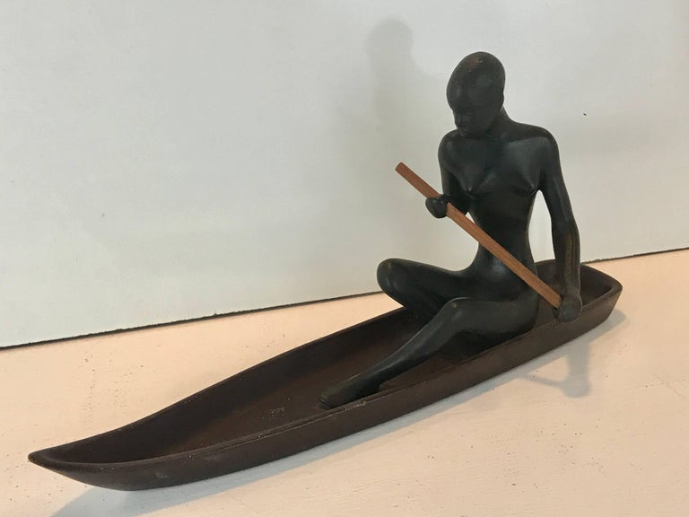 Hagenauer Style Nubian Sculpture, by Gmundner Keramik, The nude female figure with wood paddle seated in a brown enameled 2 inch wide canoe, retains original paper label
