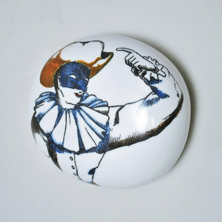 Porcelain pebble paperweight with a decor of a character from the Commedia dell'arte: Pulcinella (Punchinello) by Piero Fornasetti, circa 1950. Signature under the base.