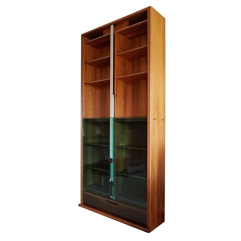 Zibaldone bookcase was designed by Carlo Scarpa in 1977 for Bernini. This tall Vintage bookcase is made in smoked walnut. It has a pair of green glass doors that slide vertically, balanced by a set of counterweight located in the central division.