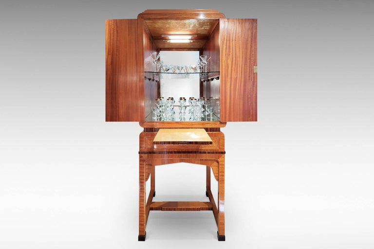 This a superb quality Art Deco cocktail cabinet with veneers and banding in burr walnut, satinwood, mahogany, Macassar ebony and others. It has a mirrored and illuminated interior with glass shelf, together with a pull-out shelf and drawer below.