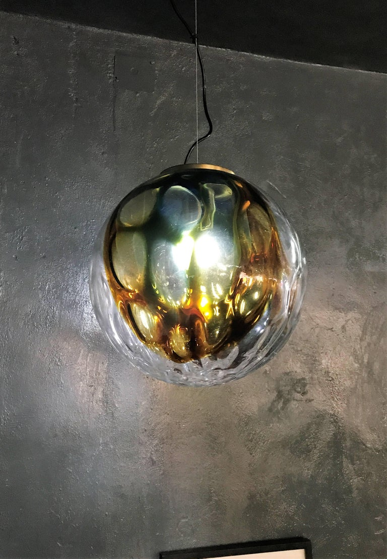 Beautiful and large pendant light in clear glass with green and amber tones attributed to Venini, circa 1970.