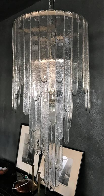 Mid-Century Modern chandelier by Carlo Nason for Mazzega consisting of three stages of clear glass blades. This chandelier is complete as there is not one inch of space free where the blades hang from. It measures 114 cm tall in its current