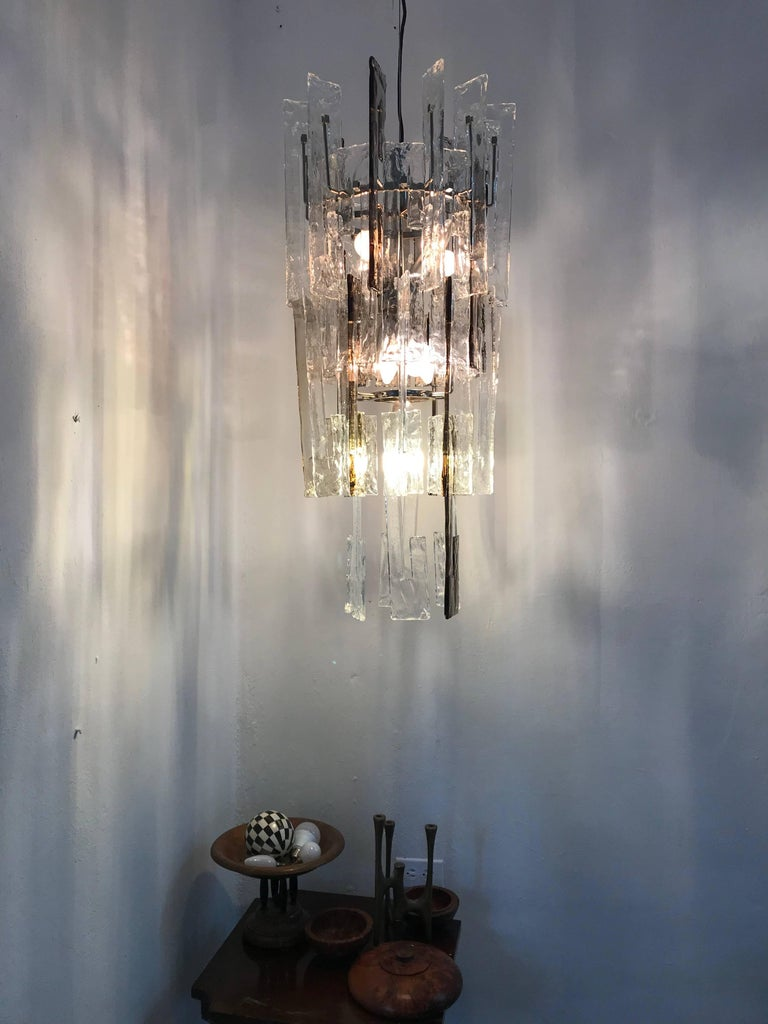 Beautiful Mid-Century Modern chandelier consisting of interlocking C shaped glass links in clear and smoked Murano glass and a Metal structure with 9 lights. Designed by Carlo Nason and produced by Mazzega, circa 1960.