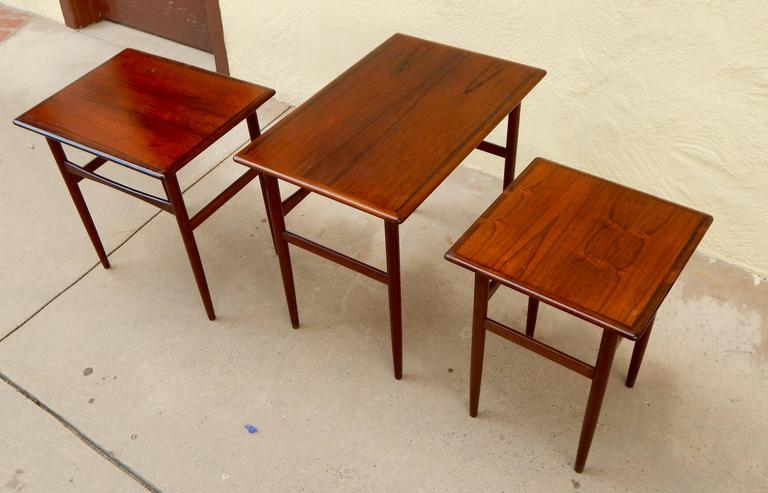 Set of three Swedish Mid-Century Modern rosewood nesting tables, circa 1950. Please see the detail photographs to see the underside hinges which house the smaller table. These are in excellent antique condition in original finish. Please contact us