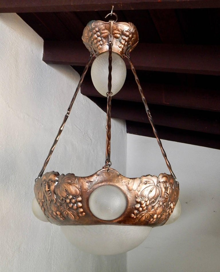Swedish arts and crafts hanging fixture composed of hammered copper and Frosted glass. All shades are original. There are a total of five electrical sockets on this fixture, all with standard bases. Price includes complete rewiring. Sweden 1910