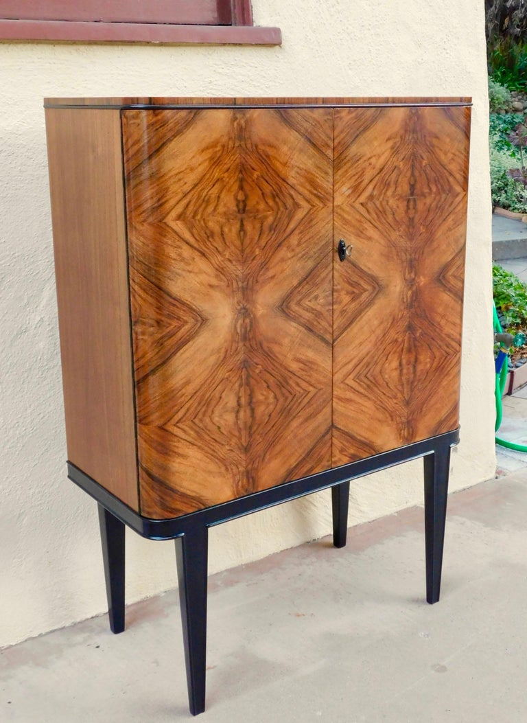 Swedish art moderne dry bar or sideboard in bookmatched, highly figured walnut. Made at Lingstroms in Sweden, circa 1940. Interior is composed of drawers and adjustable/removable shelves-you can see the shelves (they are not pictured assembled) in