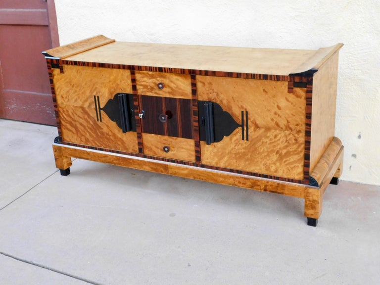 Swedish Art Deco sideboard rendered in highly figured, bookmatched golden flame birch wood. Accented with rosewood and ebony. WIth all original bakelite handles. Interior is composed of drawers and one shelved cabinet, one cabinet without shelf. In