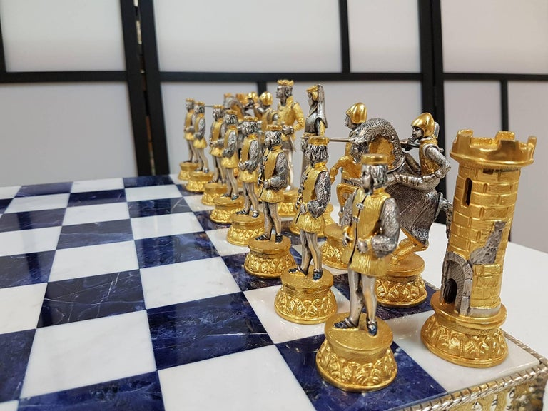Sterling silver bi-color chessboard and chess game in medieval style. The chessboard is in molten silver with blue lapis and white color marble on four horses Total 10,000 grams.