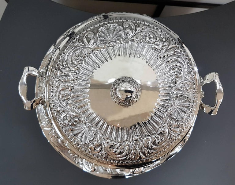Sterling Silver Baroque style tureen with handles and base. The round shape is embellished with chisels,  typical of the Baroque style. The tureen is placed on a round waved plate which is also circular with the same chisel pattern. 2,405 grams Dish