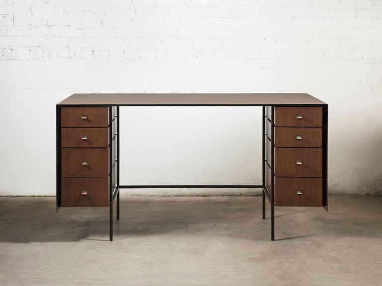 A single brass sheet is bent creating the surface and sides, aptly giving the desk its name. The finish is darkened by hand through a proprietary solution and the drawers are made from solid walnut and veneered fronts. Perfect as a writing desk in