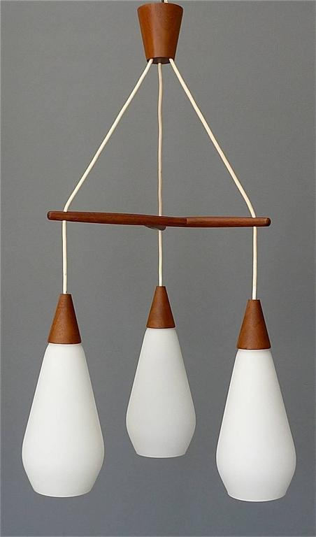 Fantastic sculptural Midcentury Scandinavian modern pendant teak lamp made around 1960 with attribution to Uno & Östen Kristiansson for Luxus / Sweden. The gorgeous light has three opaque white glass shades with satin finish hanging on a teak wood