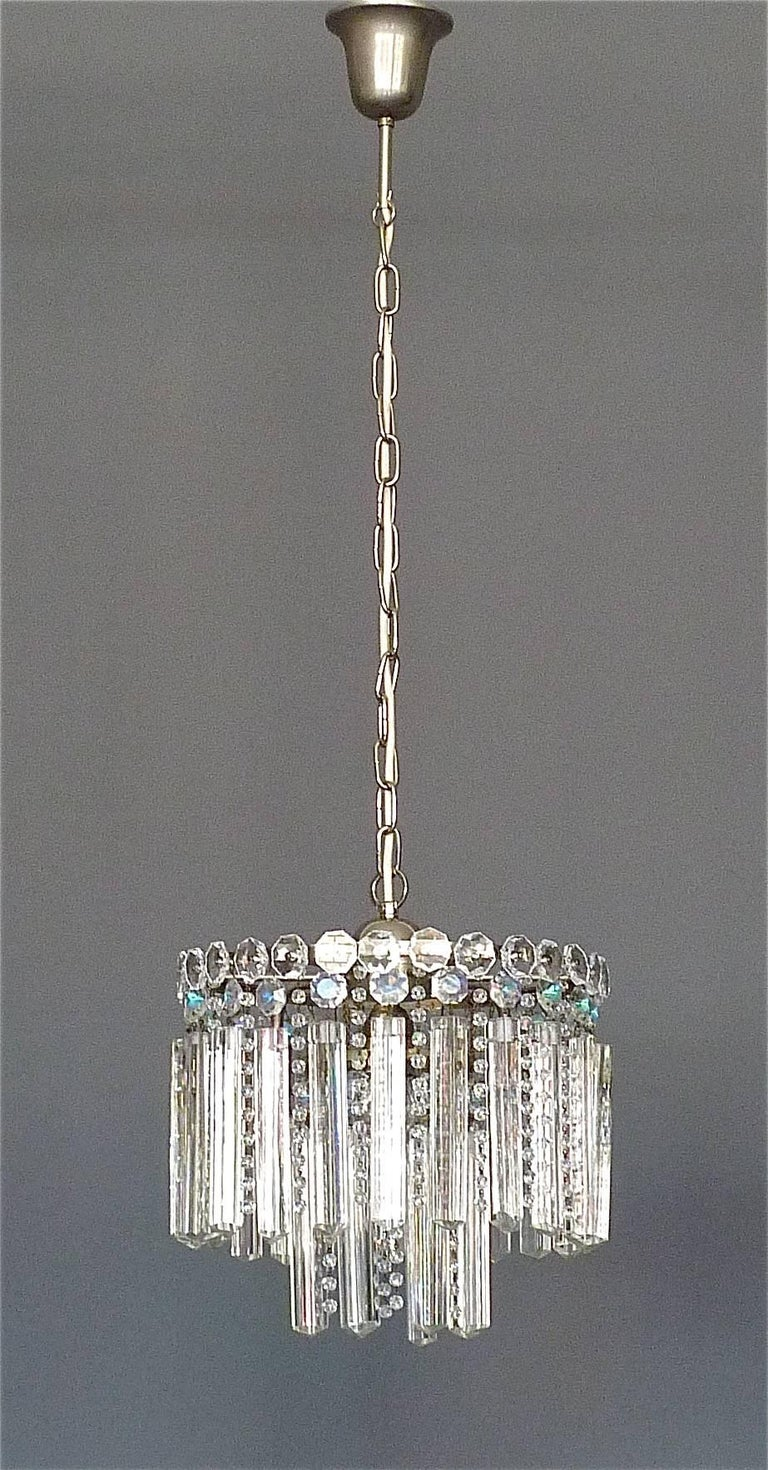 Precious faceted crystal glass chandelier made by Lobmeyr or Bakalowits, Vienna, Austria, circa 1950s. The chain-hanging length-adjustable two-tier chandelier has three-sided elongated hand-cut crystal glass sticks and lots of high lead hand-cut