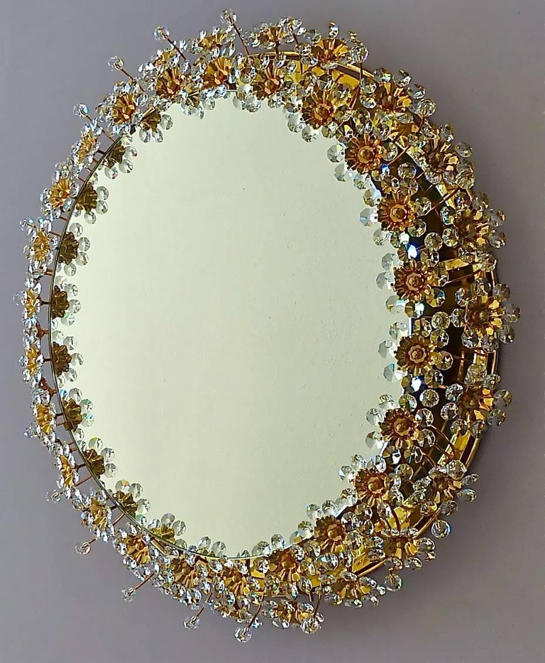 Amazing round gilt brass metal crystal glass backlit wall mirror made by Palwa, Germany, circa 1960-1970, documented in the Palwa sales catalog. The frame has lots of beautiful hand-cut faceted crystals in the shape of flowers which sparkle like