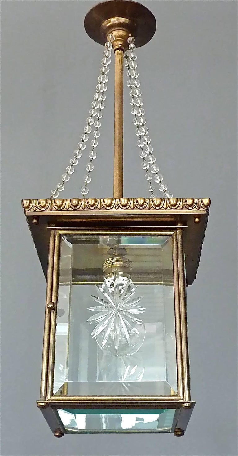 Signed Vienna Secession pendant lamp or lantern, Austria, circa 1905. Antique patinated brass metal lamp corpus with nice Art Nouveau / Jugendstil details, glass pearl strings which come from the canopy, hinged door with impressed XX, unidentified