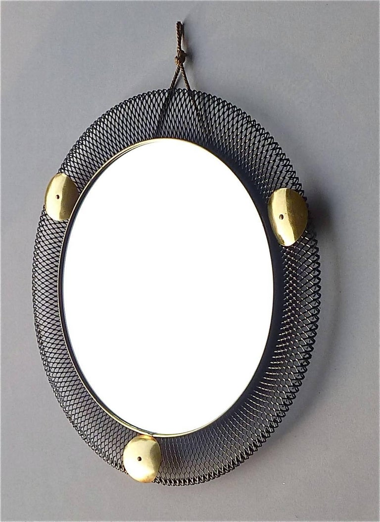 Round midcentury wall mirror which is made in the style of Jacques Biny, Mategot or Pierre Guariche, France or Italy, circa 1955. It is made of black lacquered or enameled stretched metal, lovely patinated brass details, mirror glass and its