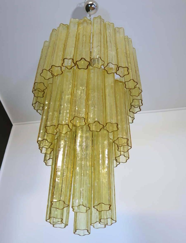 Italian vintage chandelier in Murano glass and nickel-plated metal structure. The polished nikel armature supports 48 large amber glass tubes; it comes complete with chrome chain and ceiling canopy.