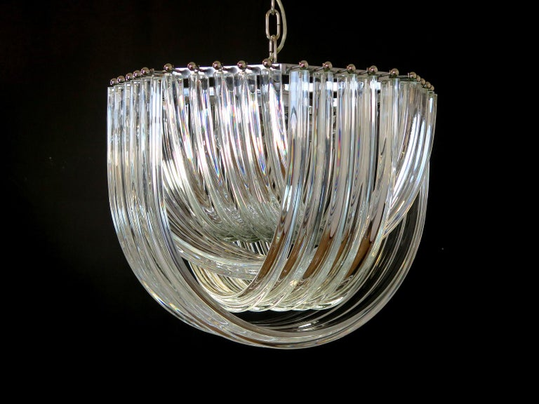 "Murano light transparent glass chandelier with four layers of curving ""triedri"" glass prisms on an octagonal chrome structure. A dynamic form, changing as you move around it, due to the overlapping levels of transparent glass with light shining"
