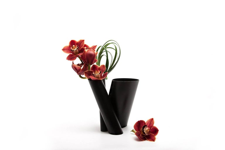 Three vases in one, composed of a series of black minimal hand-painted stainless steel tubes in various dimensions and cut on the bias, the contemporary Bana Triple vase can uniquely accommodate a single stem to full flower arrangements separately