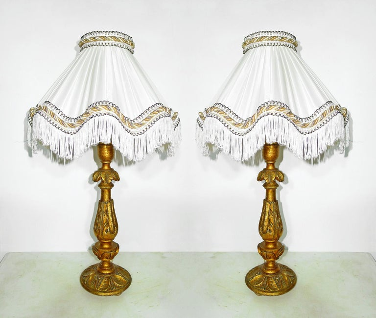 Pair of elegant Italian Baroque carved giltwood candlesticks torchères turned into table lamps with ivory silk lampshades Measures: Height: 24 in /60 cm Diameter: 14 in /36 cm Weight: 5 lb. /2,5 kg Housing one light bulb each ( E14 ) Good