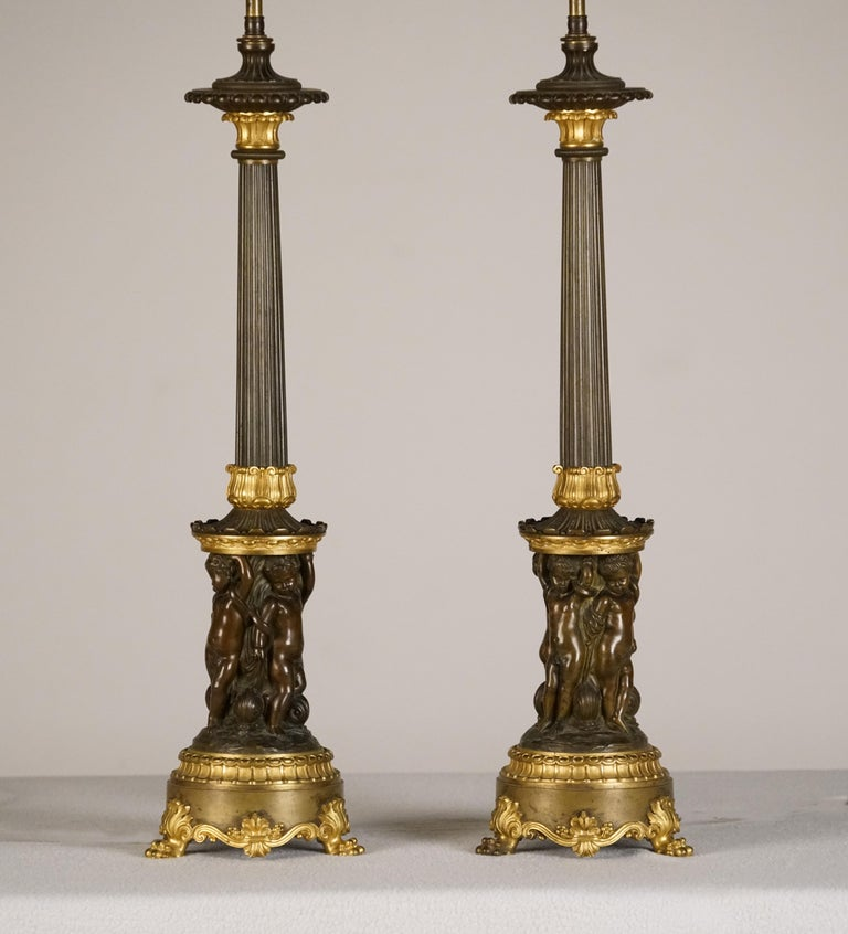 A fine pair of empire patinated & gilt bronze Candelabre, mounted as lamps 1st quarter of the 19th century  Each reeded stem above drum base relief-cast with four putti on leaf-backed lion's paw feet.  Height 24 ½ in. Lamp Height 36 ¼