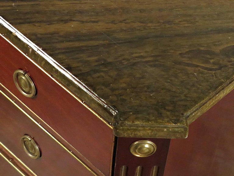 A Russian Neoclassical Brass Mounted Mahogany Commode  Early 19th Century   The rectangular faux marble top with outset square corners, above a conforming case fitted with three long graduated drawers, flanked by fluted stiles headed by roundels and