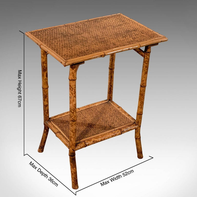 A most pleasing antique Victorian table presented in good antique condition Of Classic two-tier design offering perfect use as a lamp or display table Orignal woven cane surfaces to upper and lower levels Rising from a swept let set in to the