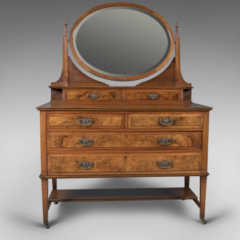 This is a stunning antique dressing table, an Edwardian vanity chest of drawers with an ovular swing mirror, English, circa 1910. Originally made and retailed by Rose & Co. of Stockton-on-Tees.