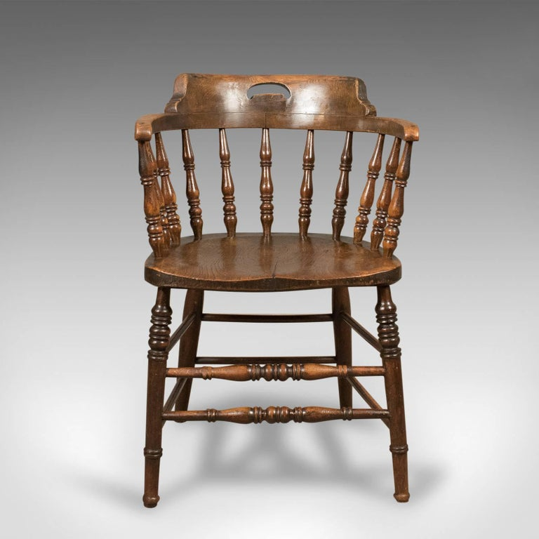 This is a Victorian, antique, low bow-back chair, sometimes referred to as a 'Smokers' or 'Captain's' chair. An English elm Windsor piece from the mid 19th century c.1870. 