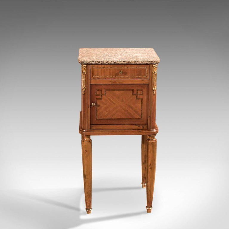 This is an antique bedside table, a mahogany pot cupboard, or nightstand, dating to the end of the 19th century.  Raised on turned, tapered fruitwood legs. The feet capped in polished bronze shoes, this fine example of a Victorian pot cupboard has