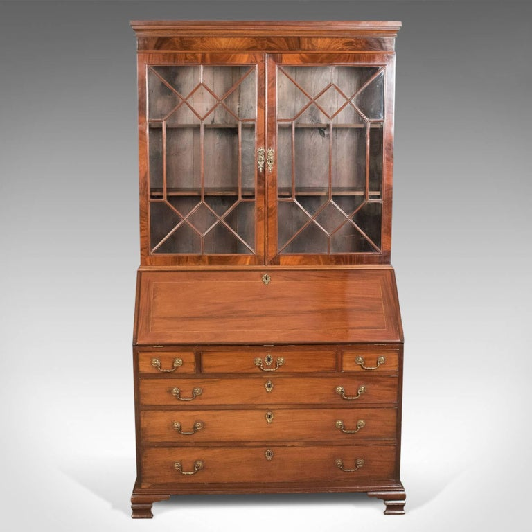 This is an antique bureau bookcase, an English, late Georgian, mahogany writing desk, circa 1800.  A very fine bureau bookcase in flame mahogany displaying good color and grain interest Featuring good proportions, useful storage, generous