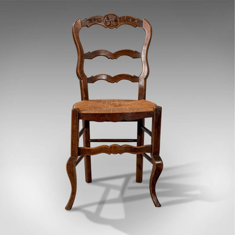 This is a set of four antique dining chairs in dark beech. French country kitchen chairs dating to the late 19th century, circa 1900.
