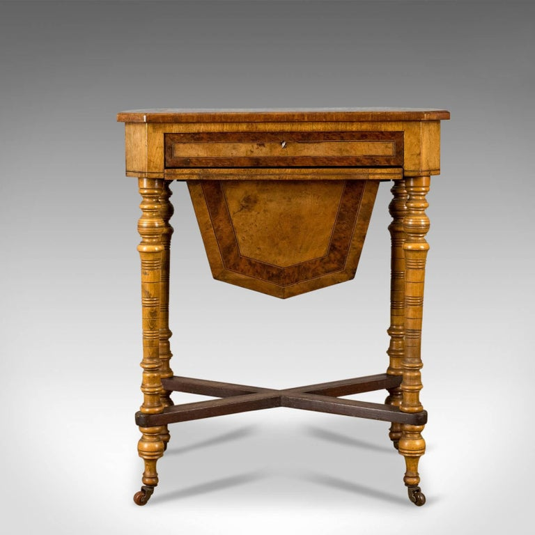 This is an antique work table, a Regency sewing table in burr walnut and amboyna, English dating to circa 1820 and later.