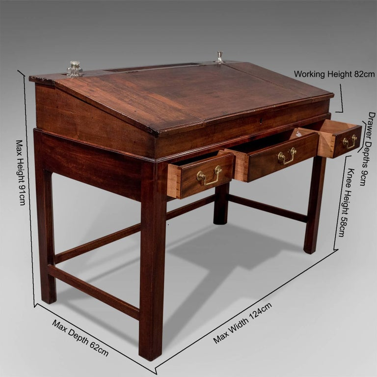 This is an antique school master's desk, an English, Georgian, mahogany desk dating to the early 19th century, circa 1800.  Presented in good antique condition.  Of quality craftsmanship with attractive proportions.  Attractive mahogany showing