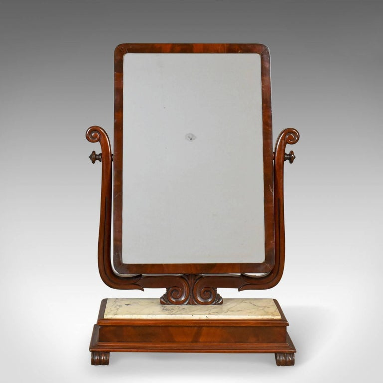 This is a large antique vanity mirror, a toilet or swing mirror, English, Victorian with a marble plinth dating to circa 1850.  A gorgeous and unusual example of a Victorian dressing mirror In mahogany and complimented by the well veined marble