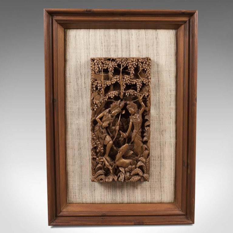 This is a framed Balinese carved wall panel, a piece of midcentury decorative art.